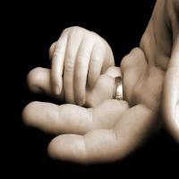 малыш держит за палец отца