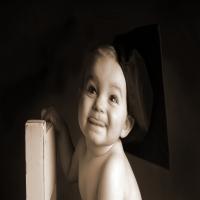 ребенок с беретом обнимает стул и улыбается